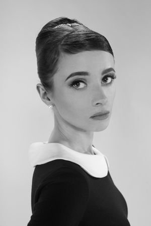 beautiful young woman in retro style with her hair in little black dress