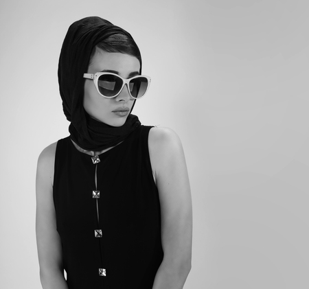 beautiful young woman in retro style with sunglasses and a head scarf black and white photography Stock Photo