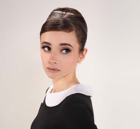 beautiful young woman in retro style with babetta hairstyle in little black dress