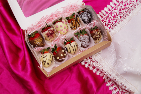 Strawberries in white and milk chocolate on a pink silk background Reklamní fotografie - 97355735