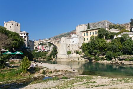 Tourists Relaxing by the River and Walking Across the Historic Old Bridge On September 24, 2010 in Mostar, Bosnia and Herzegovina