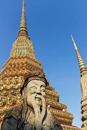 Statue of Bearded Man in Front of Colorful Chedis at Wat Pho in Bangkok, Thailand photo