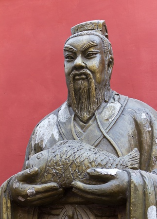 Statue of a Chinese Man Holding a Fish Outside the Confucius Temple in Beijing, China photo
