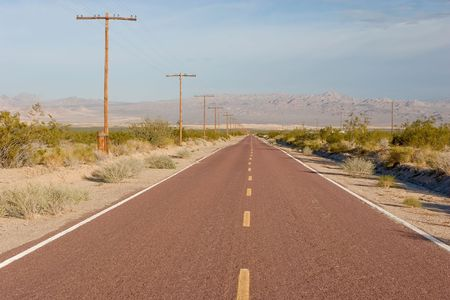 straight, empty road in the middle of nowhere. Mojave National Preserve, California photo