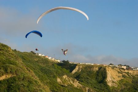vents: Paragliding is a recreational and competitive flying sport. A paraglider is a free-flying, foot-launched aircraft. The pilot sits in a harness suspended below a fabric wing, whose shape is formed by the pressure of air entering vents in the front of the w Stock Photo