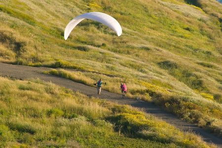 Paragliding is a recreational and competitive flying sport. A paraglider is a free-flying, foot-launched aircraft. The pilot sits in a harness suspended below a fabric wing, whose shape is formed by the pressure of air entering vents in the front of the w Stok Fotoğraf