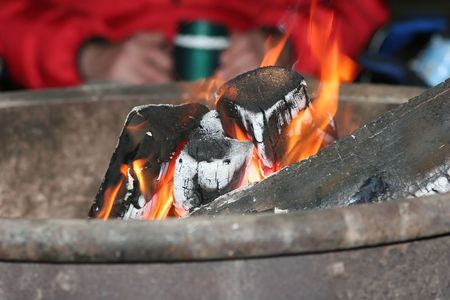 A campfire is a fire lit at a campsite, usually in a fire ring. Campfires are a popular feature of camping Stock Photo