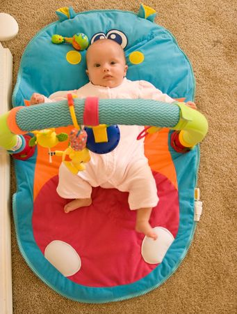 playmat: Baby girl laying on a playmat.