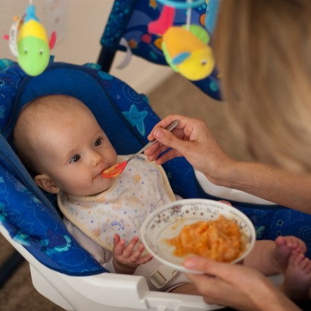 Mother is feeding little caucasian girl with solid food.