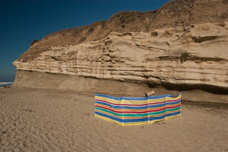 screen: A screen for protection against the wind on a beach.