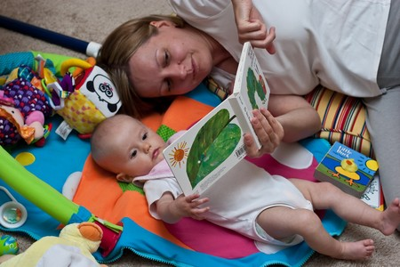 stories: Mother reading a book to little caucasian girl.