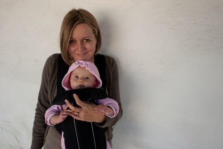 A six month old baby girl being carried in a carrier by her mother Stok Fotoğraf