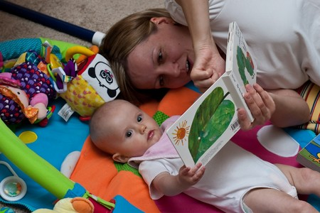 Mother reading a book to little caucasian girl.