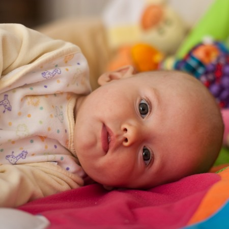 playmat: Little caucasian baby girl playing on colorful playmat.