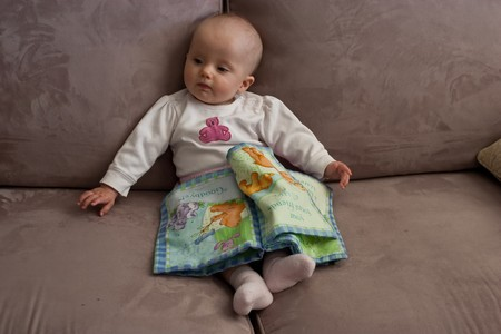 Little baby girl sitting on a sofa and playing with cloth\ book.