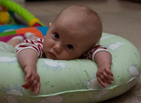 Caucasian baby girl playing on her colorful playmat. Imagens