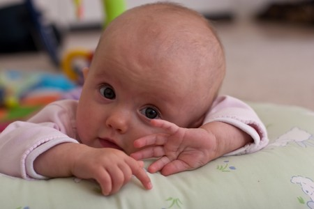 playmat: Caucasian baby girl playing on her colorful playmat. Stock Photo