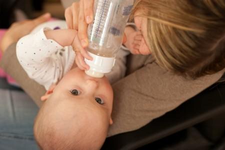 Mother feeding baby girl with bottle of milk Stock Photo - 4560949