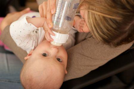 nursing bottle: Mother feeding baby girl with bottle of milk