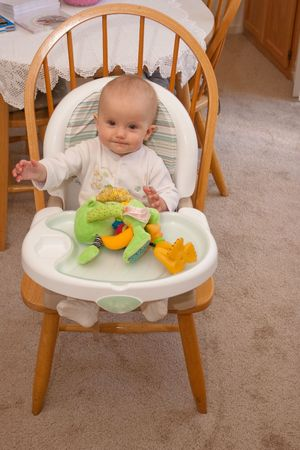 A high chair is a piece of furniture used for feeding older babies and younger toddlers. The seat is raised a fair distance from the ground, so that a person of adult height may spoon-feed the child comfortably from a standing position. photo