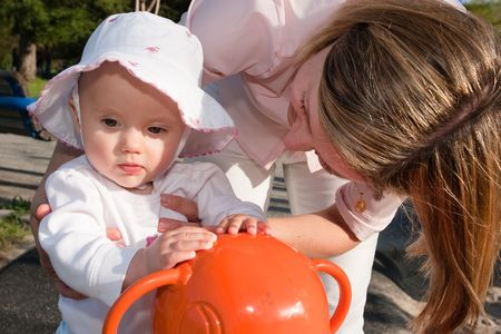 Portrait of a cute little caucasian baby girl and her mother having fun riding a spring horse photo