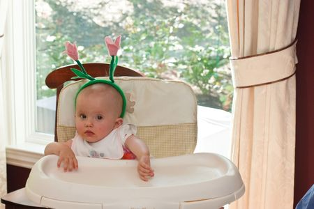 Cute baby girl sitting in high chair and waiting for breakfast. photo