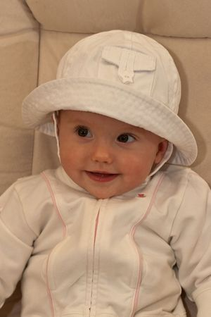 Cute little caucasian baby girl wearing white hat and sitting on a chair.