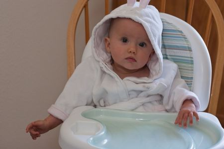 Cute baby girl in white bath robe sitting in high chair and waiting for breakfast. photo
