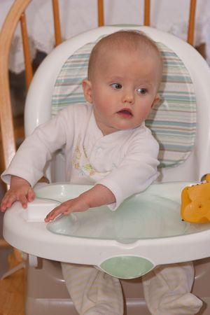 A high chair is a piece of furniture used for feeding older babies and younger toddlers. The seat is raised a fair distance from the ground, so that a person of adult height may spoon-feed the child comfortably from a standing position. Stockfoto