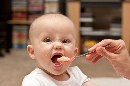 Moeder is de voeding weinig blanke meisje met havermout graansoort. Stockfoto