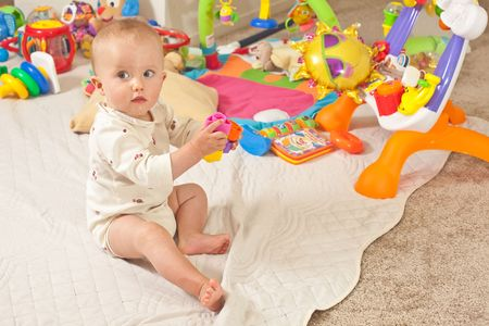playmat: Caucasian baby girl playing on a floor.