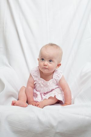 Cute little caucasian baby girl wearing pink dress on a white background