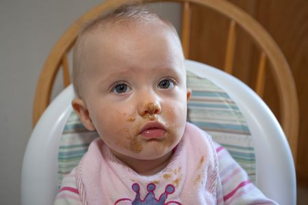 Cute little caucasian girl with oatmeal all over her face. Stock Photo - 5214057