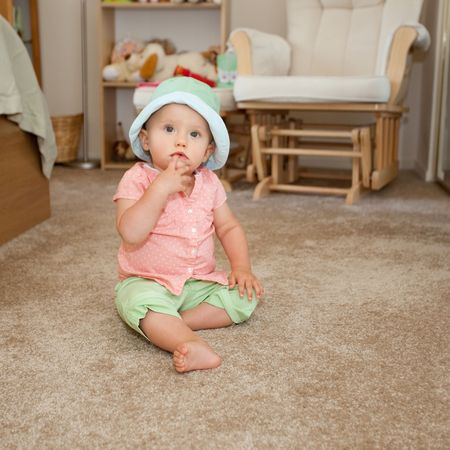 Caucasian baby girl in green hat playing on a floor.