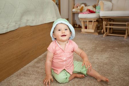 Caucasian girl in green hat playing on a floor. Stok Fotoğraf