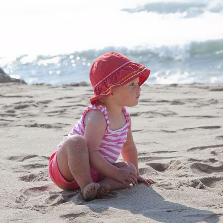 Cute Caucasian baby girl playing with the sand on the beach. Imagens - 5654207