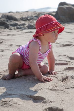 Cute Caucasian baby girl playing with the sand on the beach. Stock Photo - 5826716