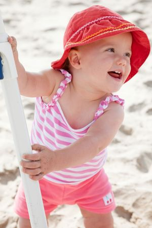 Cute Caucasian baby girl playing with the sand on the beach. Standard-Bild