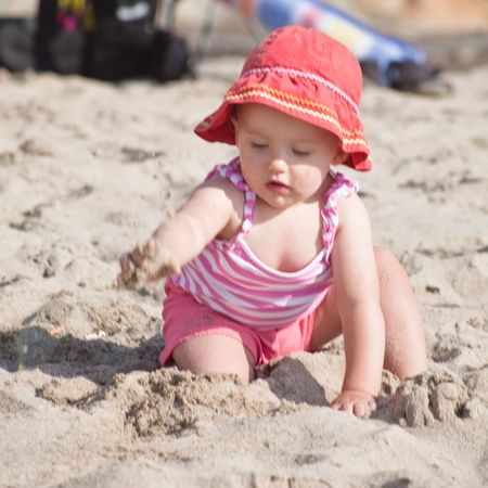 Cute Caucasian baby girl playing with the sand on the beach. Stock Photo - 5826712