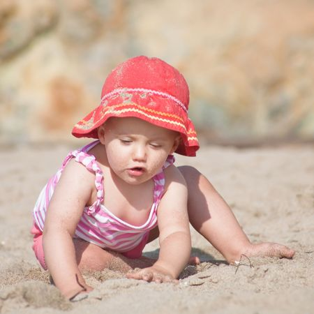Cute Caucasian baby girl playing with the sand on the beach. Stock Photo