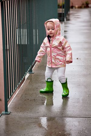 Cute caucasian baby girl wearing pink raincoat and green rubber boots. photo