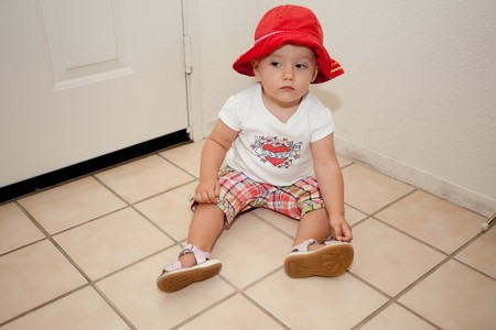 Cute Caucasian baby girl playing on a floor.