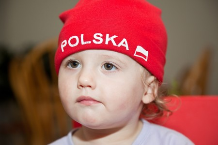 Caucasian baby girl in red hat playing at home