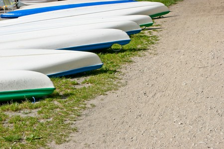 ashore: White flat-bottomed boats ashore for storage.