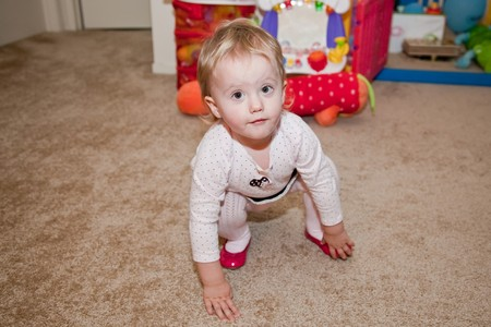 Caucasian baby girl playing on a floor.