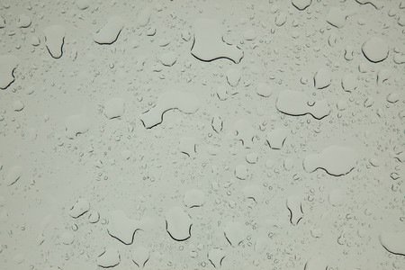 Rain drops on window glass with blurry view behind.
