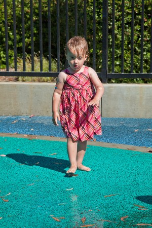 Cute little European toddler girl having fun with water at the playground in park photo