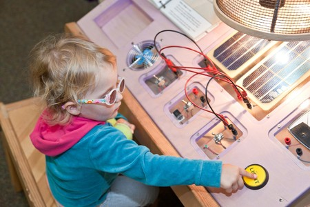 Cute little European toddler girl learning about solar power in museum Banco de Imagens
