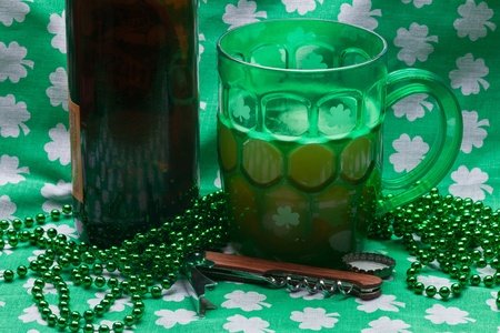 Beer mug, beads, bottle opener on a green material on wooden table. Stock Photo - 8898844