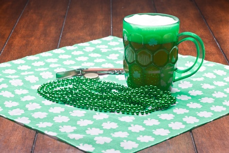 Beer mug, beads, bottle opener on a green material on wooden table. Stock Photo - 8898853